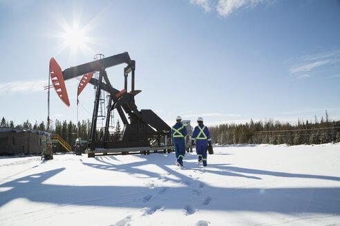 Workers walking toward drilling rigs in snow - HEROF27010