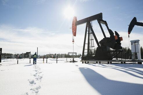 Worker walking toward drilling rigs in snow - HEROF27031