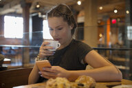 Young woman drinking coffee and texting in cafe - HEROF27061