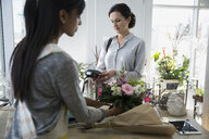 Woman paying with credit card machine flower shop - HEROF27097