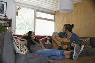 Young couple playing guitar on living room sofa - HEROF27115