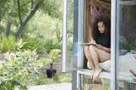 Young woman writing in journal at bedroom window - HEROF27118