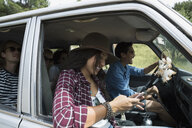Young woman texting with cell phone in car with friends - HEROF27127