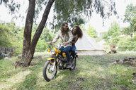 Young couple writing motorcycle outside camping yurt - HEROF27136
