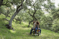 Young couple resting on motorcycle in woods - HEROF27139