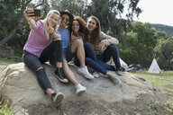 Young friends taking selfie on rock outside campsite - HEROF27142