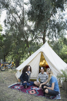 Young friends playing card game outside camping yurt - HEROF27151