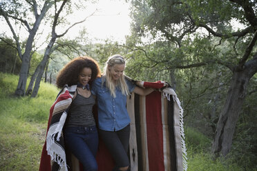 Young women walking and sharing blanket in woods - HEROF27154
