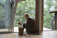 Woman and dog sitting in patio doorway - HEROF27157
