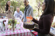Woman serving birthday cake at patio table - HEROF27166