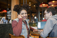 Portrait smiling girl sharing headphones with boy in coffee shop - HEROF27250
