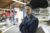 Portrait confident young mechanic in auto repair shop - HEROF27268