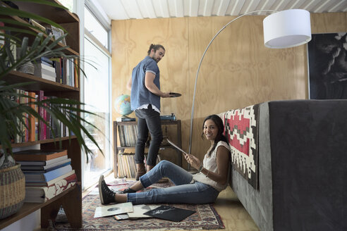 Portrait smiling young couple looking at vinyl records in living room - HEROF27289