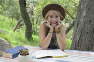 Portrait smiling young woman writing in journal at patio table - HEROF27295