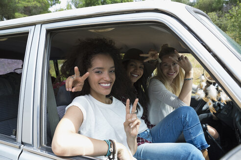 Portrait smiling young women gesturing peace sign in car - HEROF27298