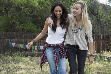 Smiling young women walking in backyard - HEROF27304