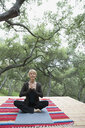Serene woman meditating with hands at heart center on deck - HEROF27316