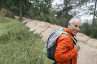 Portrait smiling mature man hiking with backpack - HEROF27325