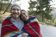 Portrait smiling couple hugging wrapped in a blanket outdoors - HEROF27337