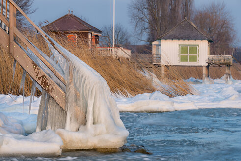 Switzerland, Thurgau, Lake Constance, Kesswil, icicles on the stairs of an old bath house and ice floes at the lake shore in the first morning light - SH02089
