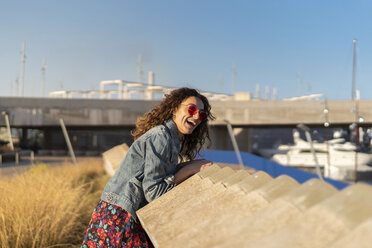 Portrait of laughing young woman leaning on a wall - AFVF02573