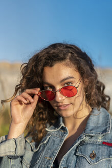 Portrait of young woman with curly brown hair wearing red sunglasses - AFVF02576