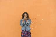 Portrait of smiling young woman throwing confetti in the air in front of orange wall - AFVF02582