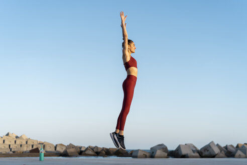 Sportive young woman during workout, jumping - AFVF02588