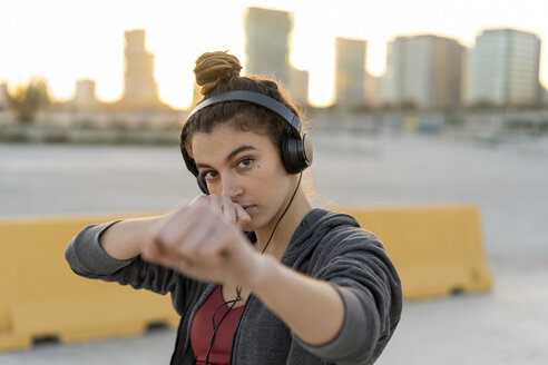 Sportive young woman with headphones during workout, boxing - AFVF02600