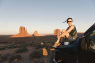 USA, Utah, Monument Valley, Woman sitting on car bonnet, enjoying the sunset in Monument Valley - GEMF02866