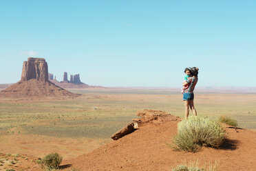 USA, Utah, Monument Valley, Mother traveling with baby girl, mother carrying girl, standing on viewpoint - GEMF02878