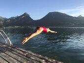 Austria, Salzburg, Salzkammergut, Salzburger Land, Wolfgangsee, St. Wolfgang, woman jumping into refreshing lake - GWF05984