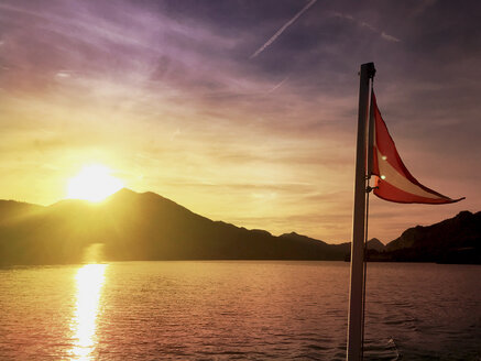 Austria, Salzburg, Salzkammergut, Salzburger Land, Wolfgangsee, Austrian National Flag of tourboat at sunset - GWF05990