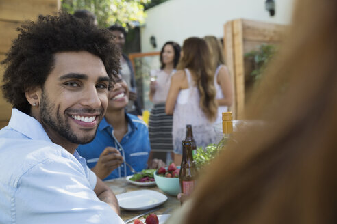 Portrait smiling man eating lunch at patio table - HEROF27428