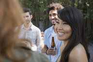 Smiling friends talking on patio - HEROF27431