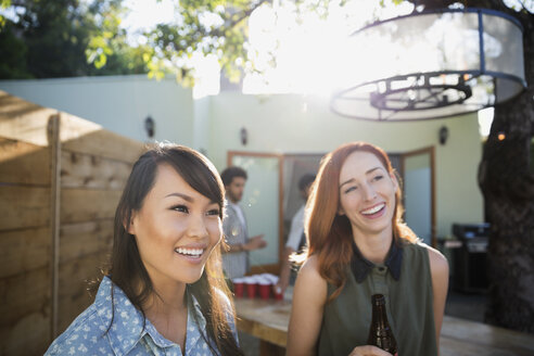Smiling friends drinking beer on sunny patio - HEROF27434