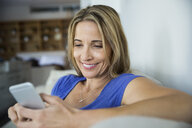 Smiling blonde woman texting with cell phone - HEROF27446