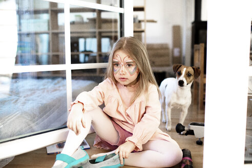 Blond girl made up as butterfly sitting on the ground, jack russel terrier in the background - KMKF00797