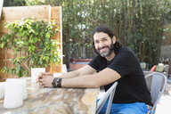 Portrait smiling bearded man sitting at patio table - HEROF27480