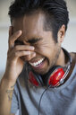 Man with headphones laughing with head in hands - HEROF27486