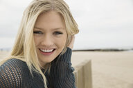 Portrait smiling blonde woman at beach - HEROF27513