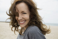 Portrait enthusiastic brunette woman at beach - HEROF27516