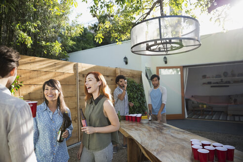 Friends talking playing beer pong on sunny patio - HEROF27540