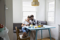 Homosexual couple hugging and texting cell phone breakfast - HEROF27561