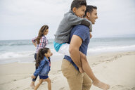 Family walking and piggybacking on beach - HEROF27594