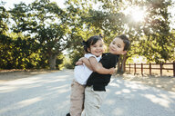 Portrait of brother carrying cute sister while standing on road against trees in park - CAVF62717