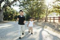 Portrait of happy cute siblings running on road against trees in park - CAVF62720