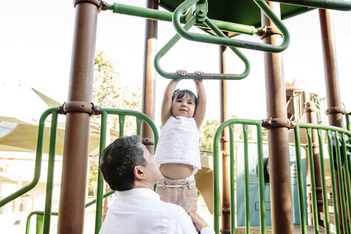 Side view of father assisting daughter in hanging on monkey bars against clear sky at playground - CAVF62723