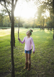 Cute girl holding stick while standing on grassy field against trees in park - CAVF62729