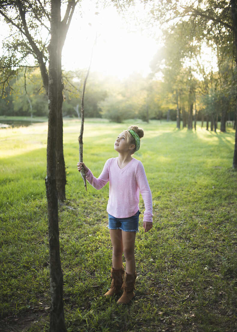 Cute girl holding stick while standing on grassy field against trees in park - CAVF62729 - Cavan Images/Westend61